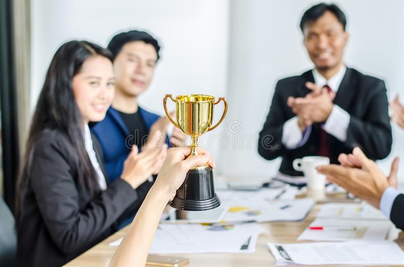 Winning business team gold trophy , business team happy consent and successful business team rewarded royalty free stock photos