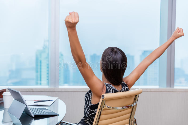 Winning office working woman arms up in success stock photography