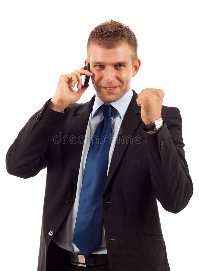 Winning on the phone. A smiling young business man discussing on a cell phone and winning, isolated on white background royalty free stock image