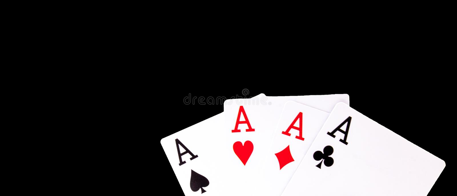 A winning poker hand of four aces playing cards suits on black background stock photo
