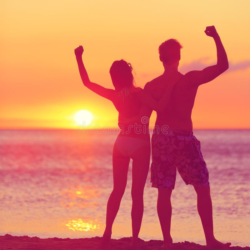 Winning success concept - happy beach couple. At sunset with arms raised up outstretched cheering and happy. Beautiful young fitness couple, men and woman stock photography