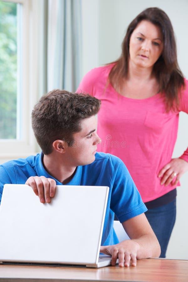 Winny nastoletni chłopak Chuje internet Wyszukuje Od matki zdjęcie stock