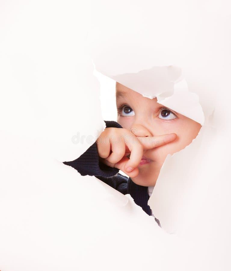Winny przyglądający dzieciak w dziurze w biały papierze obraz royalty free