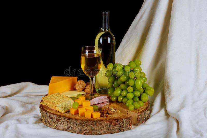 Wino i rozmaitość ser na drewnianym stołowym życiu fotografia stock