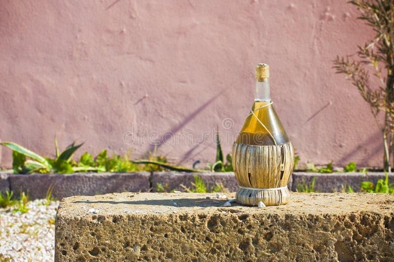 Wino kolba zakrywająca z słomianym odpoczywający na tufa kamienia bloku przeciw ścianę - wizerunek z kopii przestrzenią obrazy stock