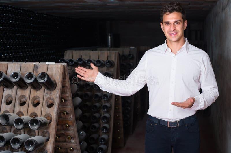Wino producent w lochu z wino butelkami składowymi zdjęcia stock