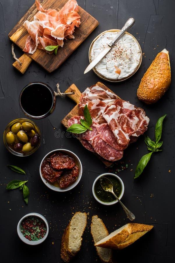 Wino przekąski set Szkło czerwień, mięsny wybór, śródziemnomorskie oliwki, suszący pomidory, baguette plasterki, camembert zdjęcie stock