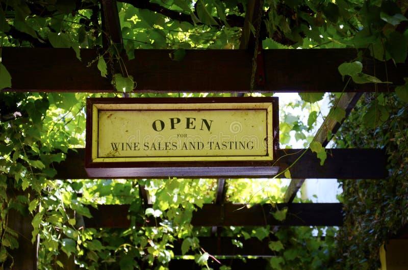 Wino sprzedaże i degustacja znaki przy uroczym wytwórnia win wejściem zakrywającym w winoroślach obraz stock