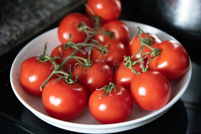 Winogradów dojrzali pomidory w białym pucharze na granitu kontuarze zdjęcie royalty free