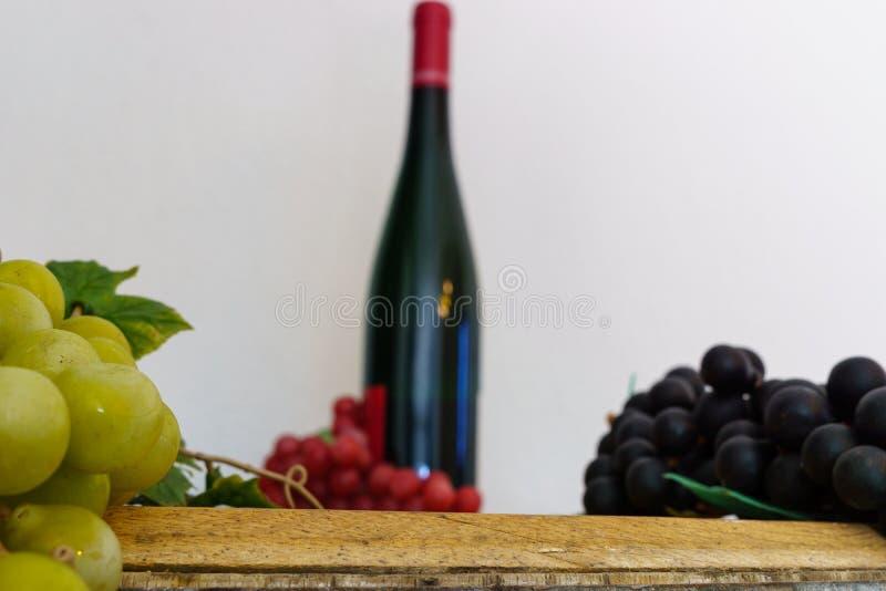 Winogrona i wino butelka na dębie beczkują obraz stock
