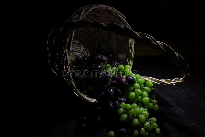 Winogrona w koszu na ciemnym tle, zbliżenie fotografia stock
