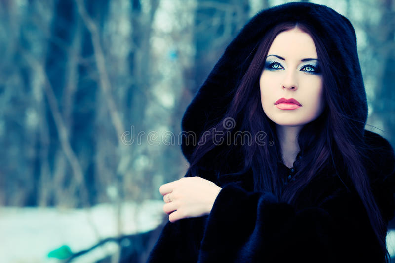 Winter. Shot of a gothic woman in a winter park. Fashion royalty free stock photo