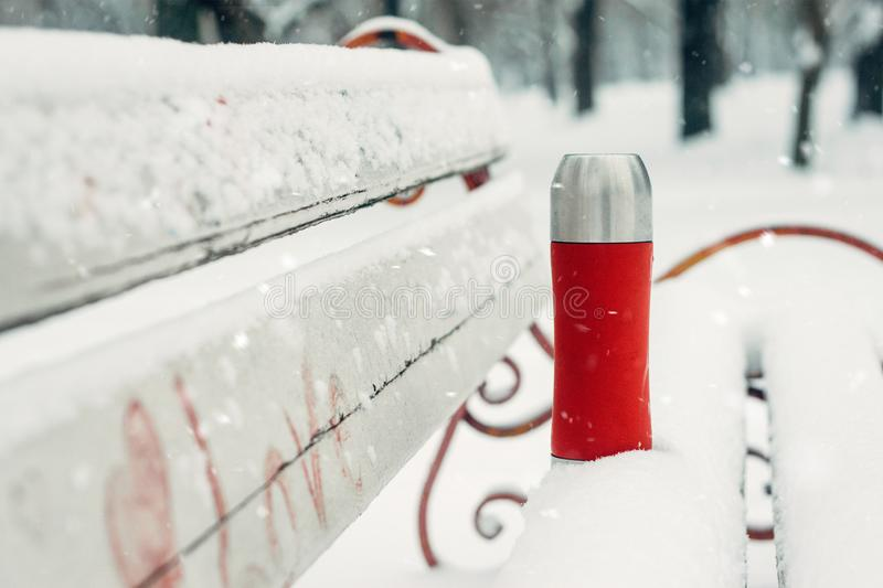 Winter Activities outdoor. Winter holidays, hot drinks concept. Red thermos and cup on snowy bench in winter park. Thermos with royalty free stock photos
