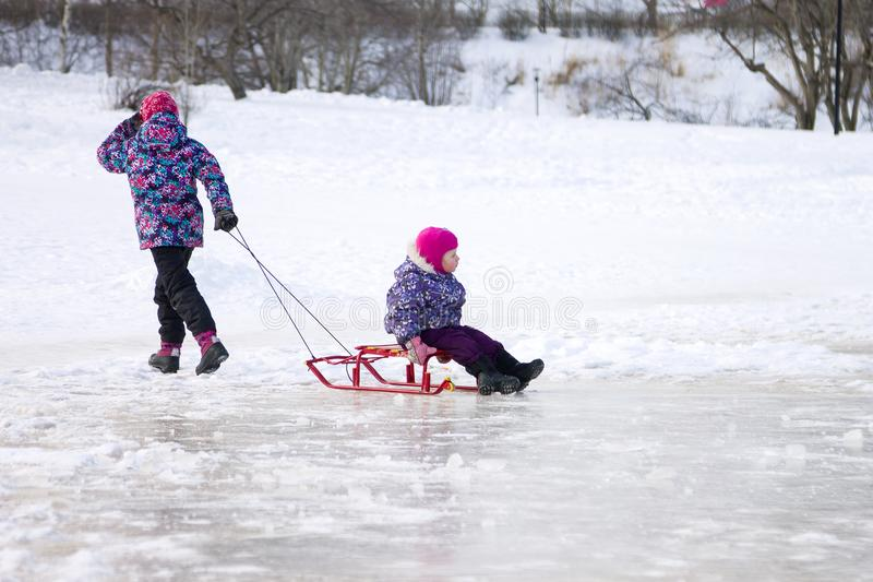 Happy ittle girl pulling her young sister on a sled on the ice in snowy winter park stock images