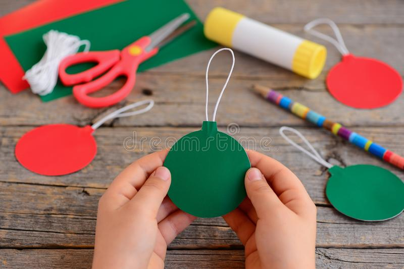 Child made red and green Christmas balls from cardboard paper. Child holds Christmas ball in his hands. Step. Stationery royalty free stock photos