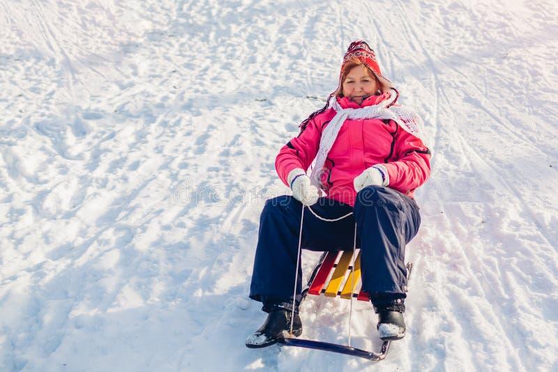 Winter activities. Senior woman sledding down on sleigh. Woman having fun in winter park royalty free stock photos