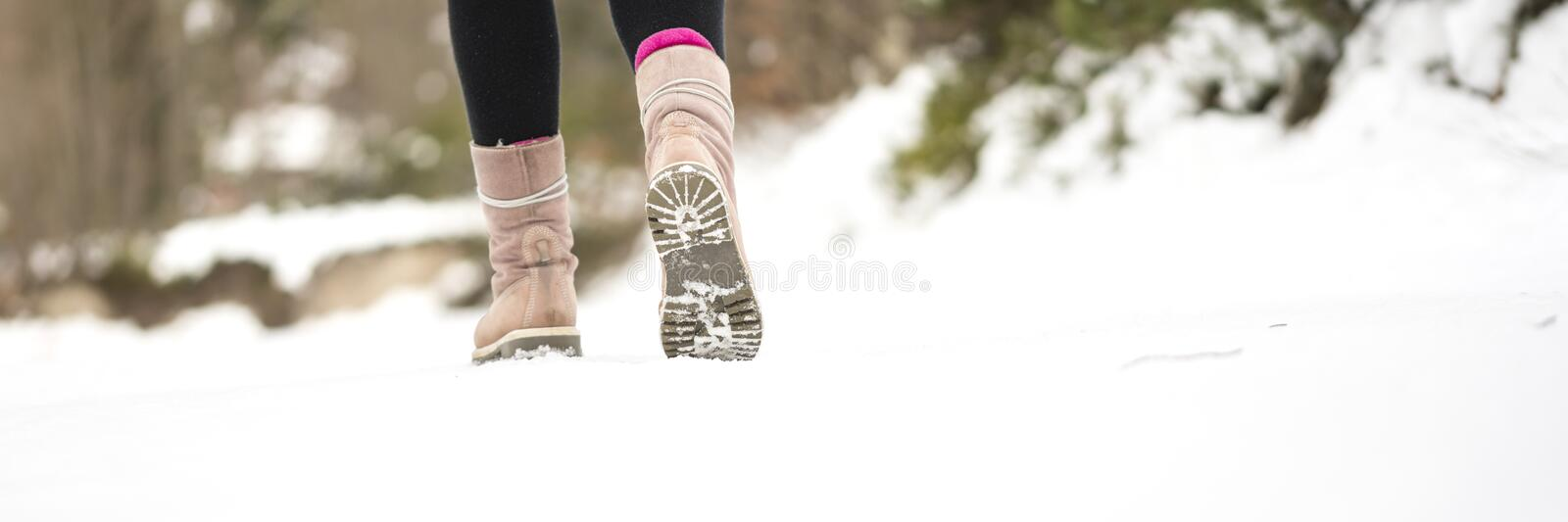Winter adventures - closeup of warm female winter boots walking stock photo