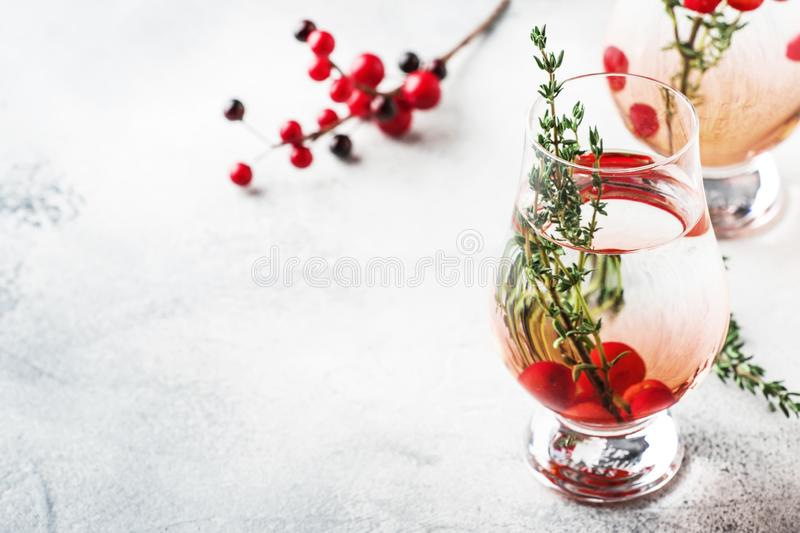 Winter alcoholic cocktail with red berries, liquor, gin, thyme and vodka for Christmas or New Year. Holiday table setting royalty free stock images