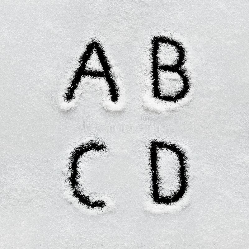 Winter alphabet, symbols and numbers hand written on snow. Black background isolated. Letters A, B, C, D royalty free stock photos