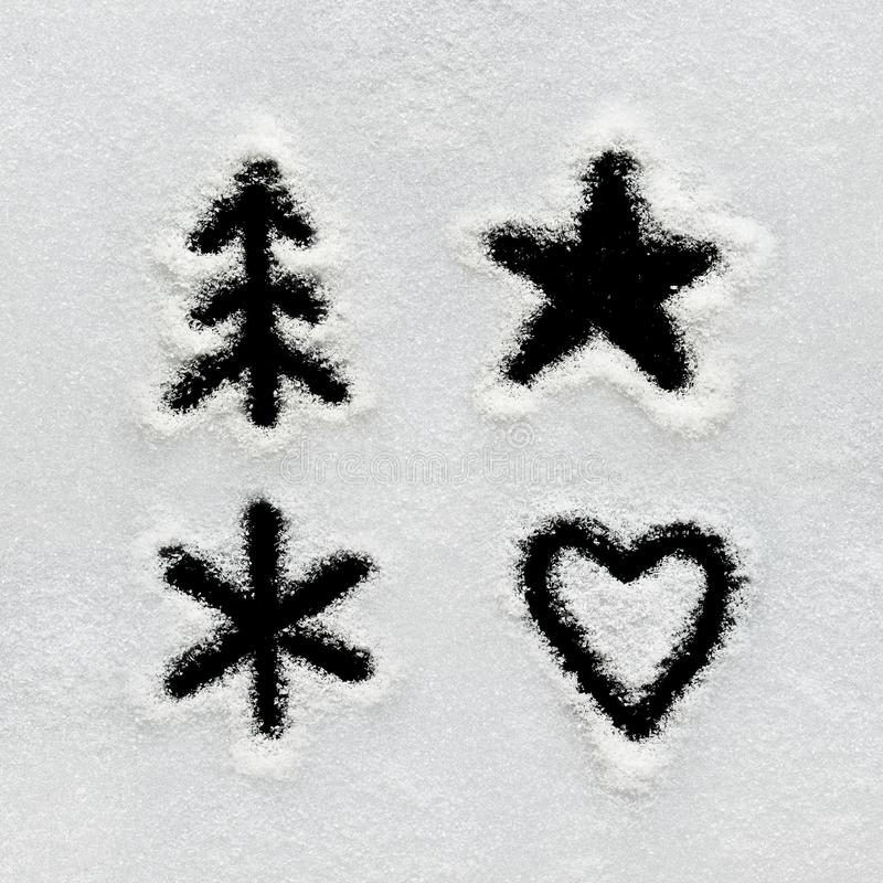 Winter alphabet, symbols and numbers hand written on snow. Black background isolated. Twig tree, star, heart, snowflake stock images