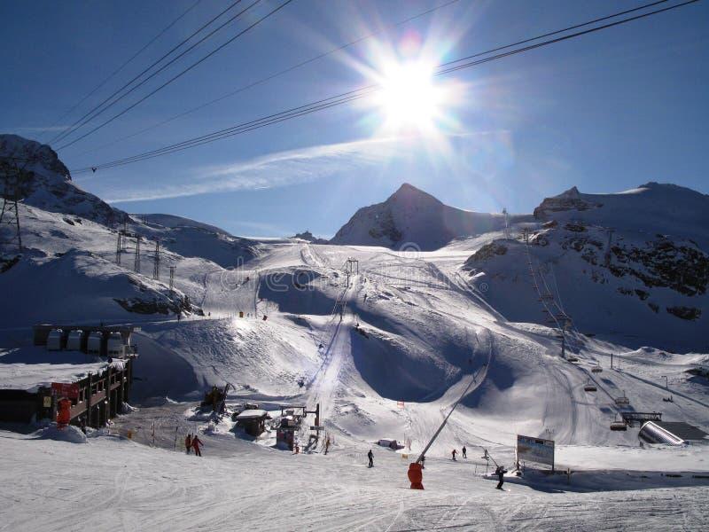 A winter alpine mountain scene under a blue sky royalty free stock photo