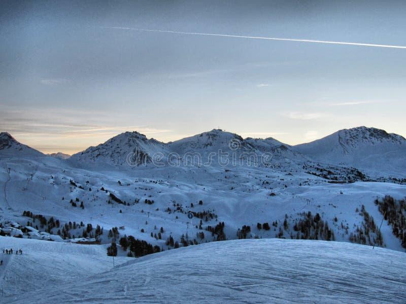 A winter alpine mountain scene under a blue sky royalty free stock photography