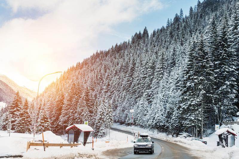 Winter alpine road curve landscape with forest, mountains and blue sky on background at bright cold sunny day. Car trip family. Travel journey. Holiday skiing stock image