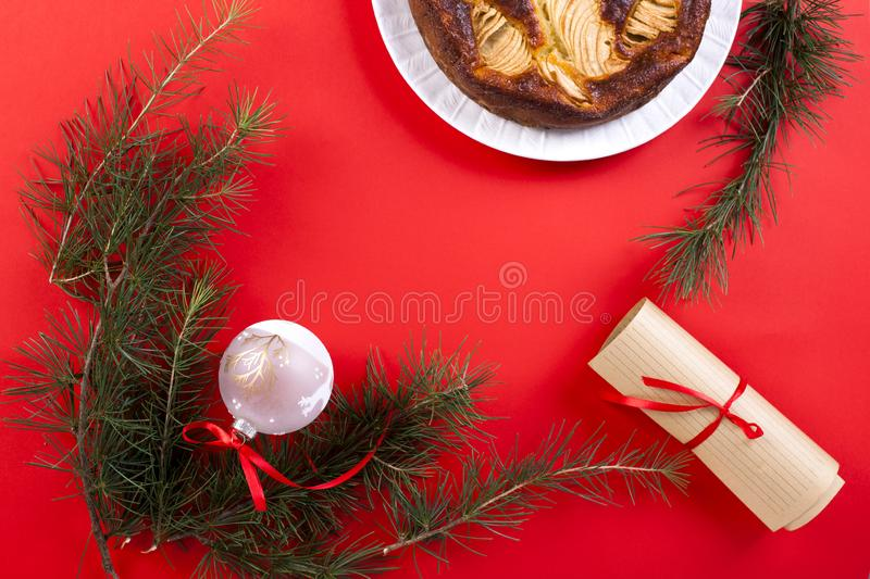 Winter apple pie on a red background. Homemade cakes. The branch. Es of the Christmas tree. Greeting card for the holiday. Top view stock image