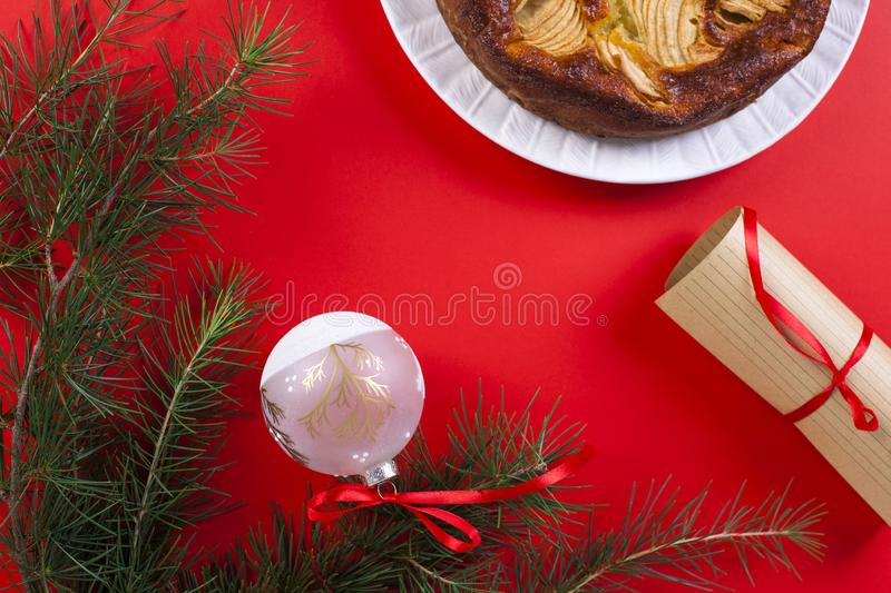 Winter apple pie on a red background. Homemade cakes. The branch. Es of the Christmas tree. Greeting card for the holiday. Top view stock photo