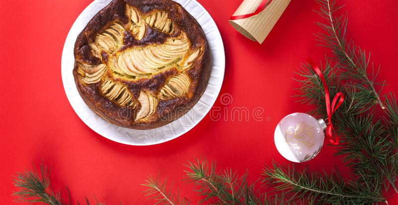 Winter apple pie on a red background. Homemade cakes. The branch. Es of the Christmas tree. Greeting card for the holiday. Top view. Banner royalty free stock images