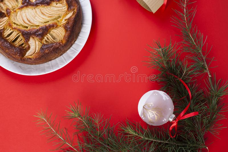 Winter apple pie on a red background. Homemade cakes. The branch. Es of the Christmas tree. Greeting card for the holiday. Top view royalty free stock photo