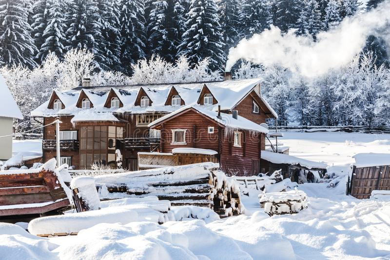 Winter architectural landscape. Of a snow-covered wooden hotel, smoke from the chimney, pine forest in the background and a lot of wooden beams in the yard stock photo