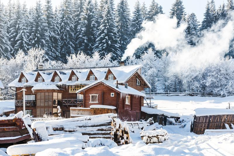 Winter architectural landscape. Of a snow-covered wooden hotel, smoke from the chimney, pine forest in the background and a lot of wooden beams in the yard royalty free stock photos