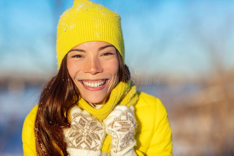 Winter Asian woman smiling in cold weather fashion accessories for winter: yellow hat and knit scarf, wool gloves, down jacket. royalty free stock photo