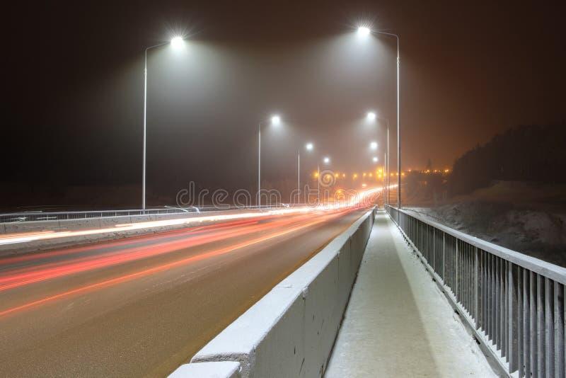 Winter auf der Brücke durch das Licht von Laternen heller Nebel und Licht vom Führen von Autos stockbild