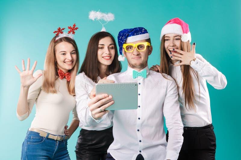 Winter-Bürofirmenmitarbeiter Thema des neuen Jahres Weihnachts Leutegeschäftslächeln-Feiertags der Gruppe 4 lustige Hüte des jung stockfoto
