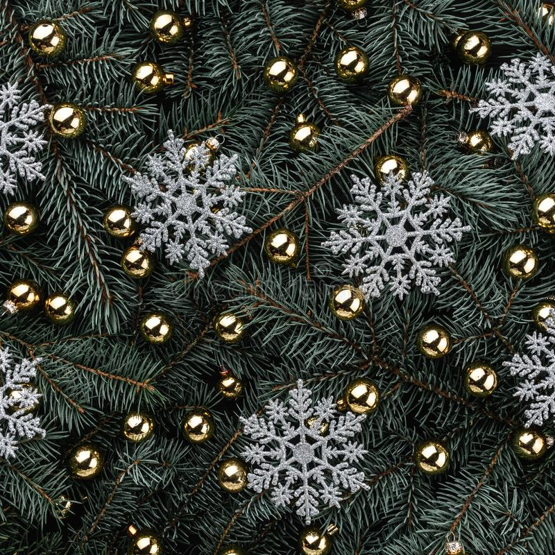Winter background of fir branches. Adorned with gold baubles. Snowflakes silver. Christmas card. Top view. Xmas congratulations. Square card royalty free stock photography