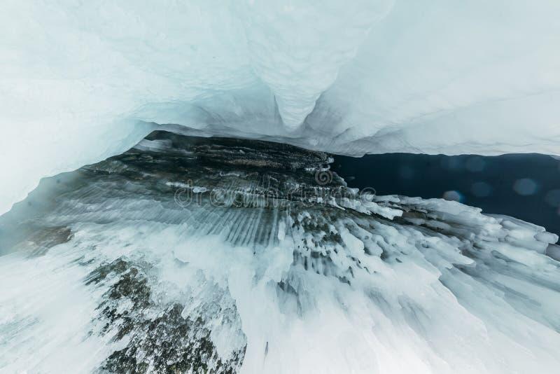 Winter Baikal Olkhon Insel Eisgrotte Starkes blaues Eis und Eiszapfen auf den Küstenfelsen von Olkhon-Insel im Winter lizenzfreie stockfotografie