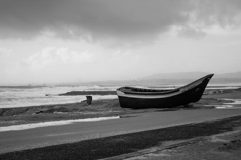 Winter on the beach, Costa de Caparica, Portugal. Winter on the beach: boat on land, sea in fury, threatening clouds, landscape deserted of people. Image taken royalty free stock image