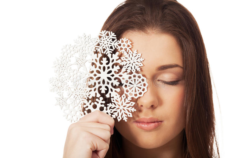 Winter bliss. Girl with big snowflake on isolated white royalty free stock photo