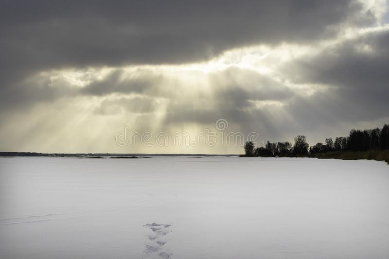 A winter blizzard is coming. Sunset over the frozen lake or river, forest. Footsteps, footprint tracks on the snow. Frosty winter landscape with frozen river or stock images