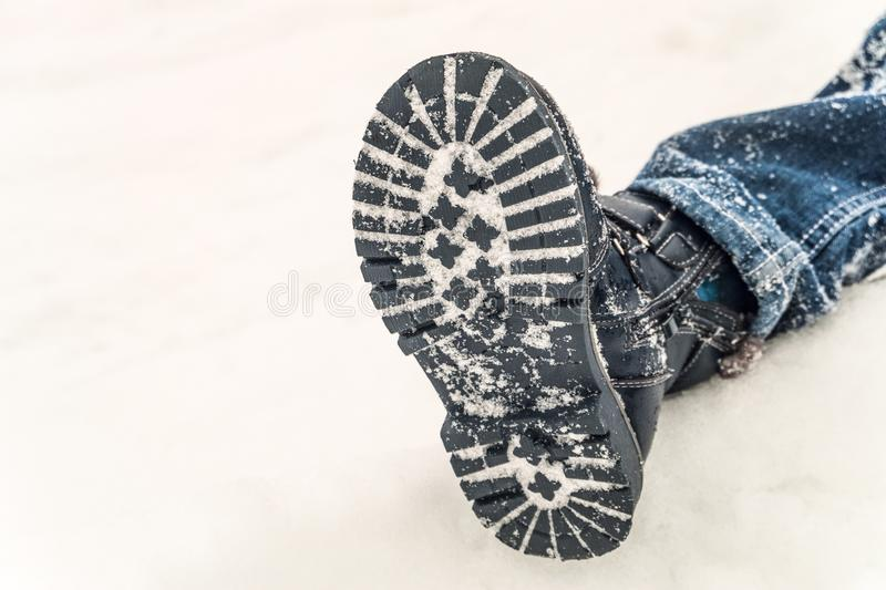 Winter boot on the feet of a boy lying in the snow. Child non-slip shoes stock photo