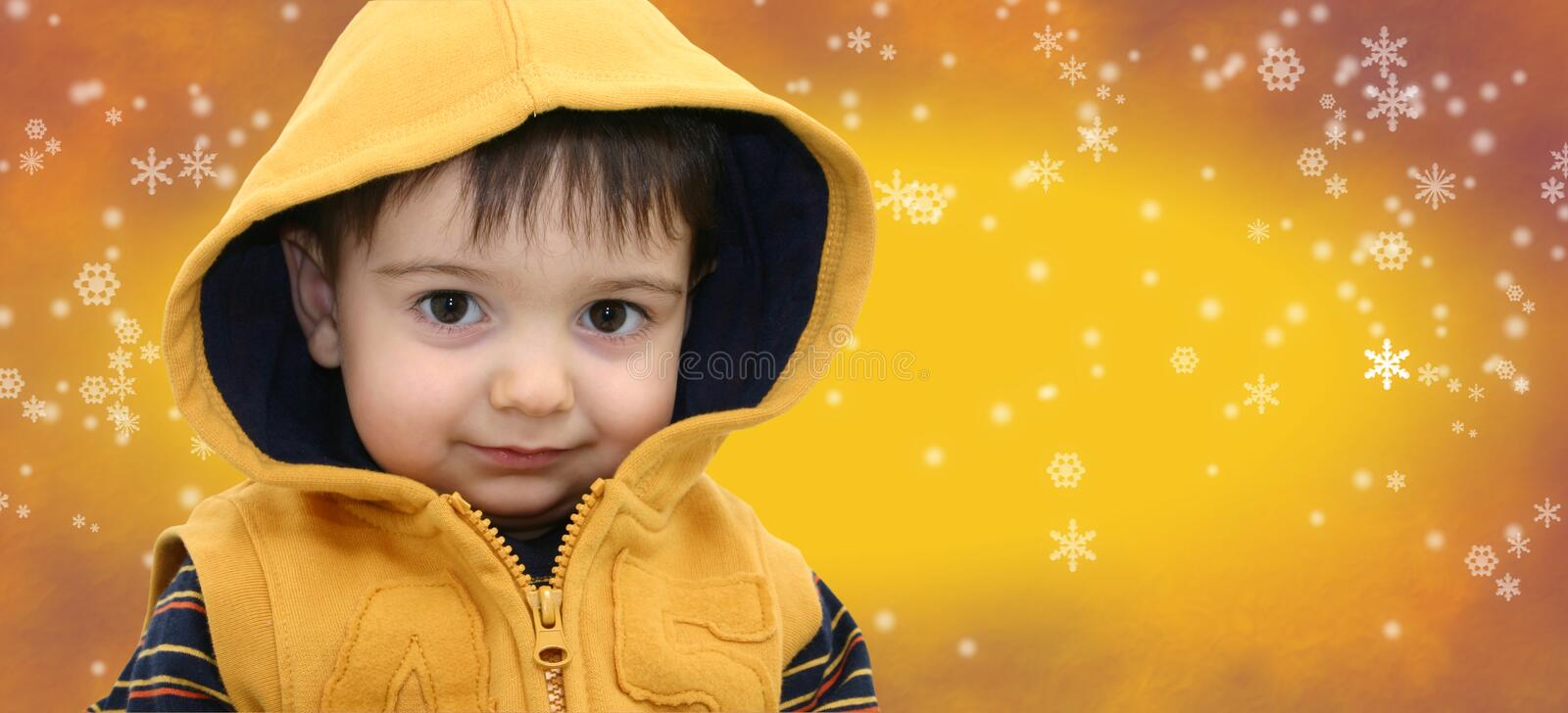 Winter Boy Child on Yellow Snowflake Background royalty free stock images
