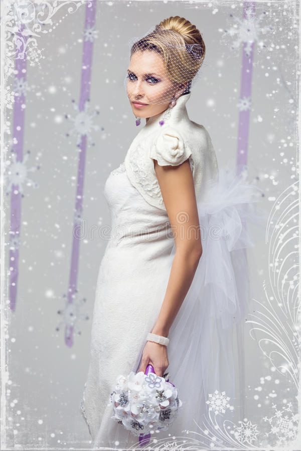 Winter bride. Portrait of beautiful young woman in long warm gown for winter wedding with purple flower bouquet. Over snowy background stock image