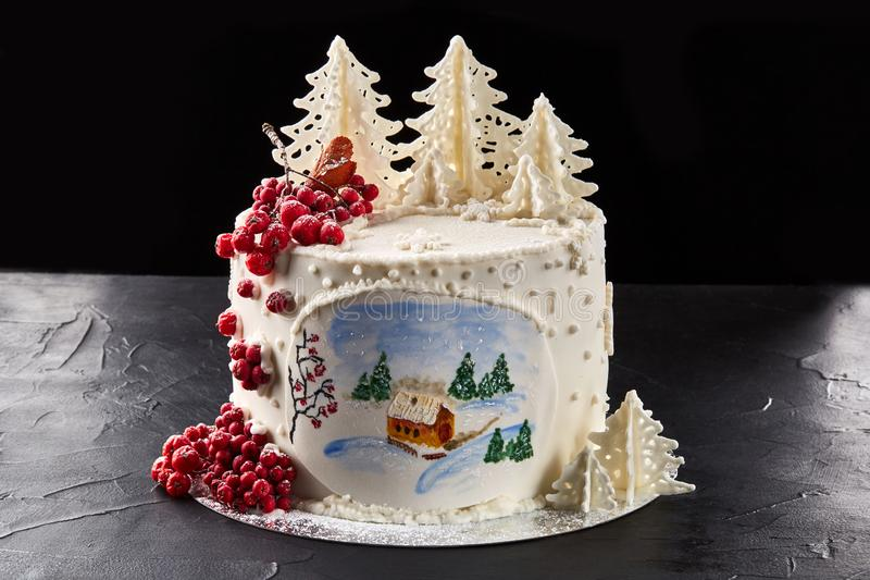 Winter cake covered with white icing, with painted house in the forest, trees and red rowan. stock images
