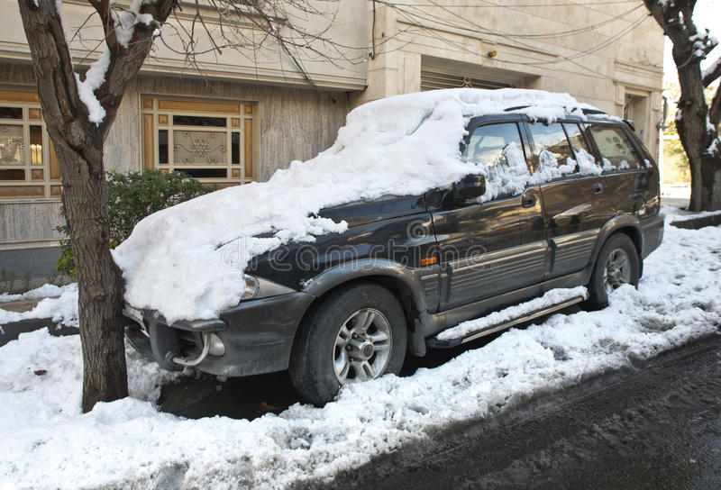 Winter car. Covered with snow having an accident with tree royalty free stock photo