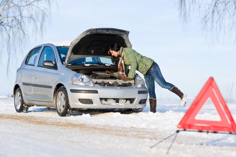 Winter car breakdown - woman repair motor royalty free stock image