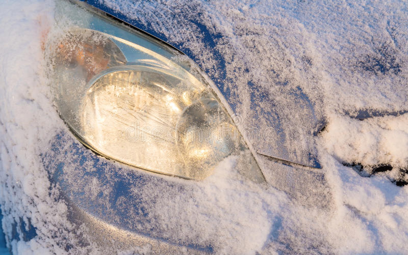 Winter Car Light. Snow freshly scrapped off a car's front light stock image
