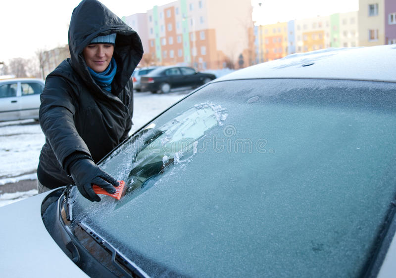 Winter car woman. Woman cleaning her car in winter stock image