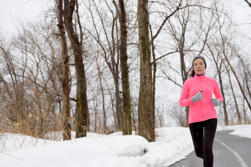 Winter cardio exercise - woman jogging running. Winter cardio exercise - woman jogging doing her workout outside. Young adult running in outdoor park with snowy stock photography